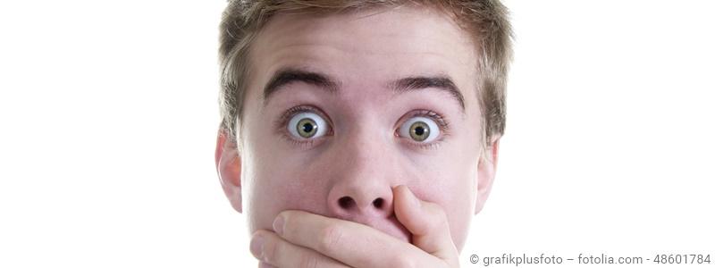 Junge schaut entsetzt und schlägt Hand vor den Mund